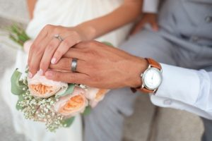 bride and groom holding showing wedding rings